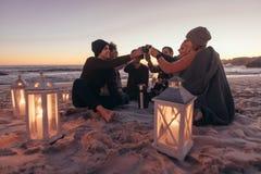 Amis faisant la fête à la plage avec du café images stock