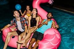 Amis faisant la fête dans la piscine Photographie stock