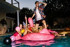 Amis faisant la fête dans une piscine dans la soirée Photo stock