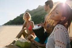 Amis faisant la fête et ayant l'amusement sur la plage Image libre de droits