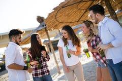Amis faisant la fête et ayant l'amusement sur la plage à l'été Image stock