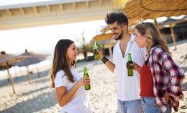Amis faisant la fête et ayant l'amusement sur la plage à l'été Photo stock