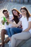 Amis faisant la fête et ayant l'amusement sur la plage à l'été Photographie stock