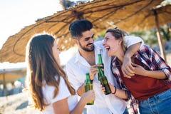 Amis faisant la fête et ayant l'amusement sur la plage à l'été Photographie stock libre de droits