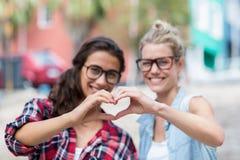 Amis faisant la forme de coeur avec des mains Image stock