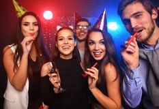 Amis faisant la grande partie pendant la nuit Cinq confettis de lancement de personnes et champagne potable Images stock
