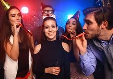 Amis faisant la grande partie pendant la nuit Cinq confettis de lancement de personnes et champagne potable Photo libre de droits
