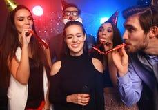 Amis faisant la grande partie pendant la nuit Cinq confettis de lancement de personnes et champagne potable Photos libres de droits