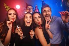 Amis faisant la grande partie pendant la nuit Cinq confettis de lancement de personnes et champagne potable Photographie stock