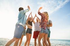 Amis faisant la haute cinq sur la plage Images libres de droits