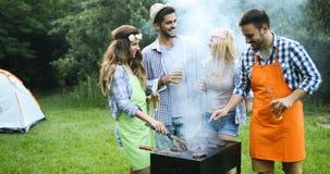 Amis faisant le barbecue et prenant le déjeuner Images libres de droits