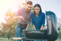 Amis faisant le barbecue et prenant le déjeuner dans la nature Couplez avoir l'amusement tout en mangeant et en buvant à un pique Images stock