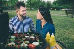 Amis faisant le barbecue et prenant le déjeuner dans la nature Couplez avoir l'amusement tout en mangeant et en buvant à un pique Photographie stock libre de droits