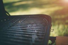 Amis faisant le barbecue et prenant le déjeuner dans la nature Couplez avoir l'amusement tout en mangeant et en buvant à un pique Images libres de droits