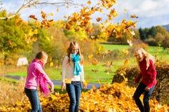 Amis faisant le diable dans des feuilles de récolte jetant le feuillage Photographie stock libre de droits