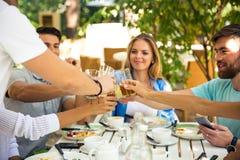 Amis faisant le pain grillé autour de la table Photo stock