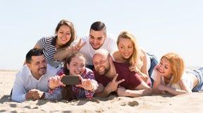 Amis faisant le selfie à la plage sablonneuse Photo stock