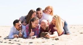Amis faisant le selfie à la plage sablonneuse Images stock