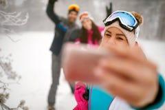 Amis faisant le selfie d'hiver dans la montagne des vacances d'hiver Photographie stock libre de droits