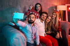 Amis faisant le selfie tout en célébrant Noël ou la soirée du Nouveau an à la maison Photo stock