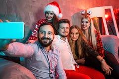 Amis faisant le selfie tout en célébrant Noël ou la soirée du Nouveau an à la maison Photographie stock libre de droits