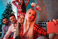 Amis faisant le selfie tout en célébrant Noël ou la soirée du Nouveau an à la maison Images libres de droits