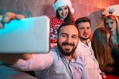 Amis faisant le selfie tout en célébrant Noël ou la soirée du Nouveau an à la maison Images stock