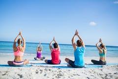 Amis faisant le yoga ainsi que leur professeur Image stock