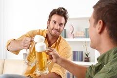 Amis faisant tinter avec de la bière Photo stock
