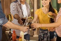 Amis faisant tinter avec des verres de kola au pique-nique sur le patio Photos stock