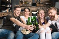 Amis faisant tinter des bouteilles à bière Photographie stock