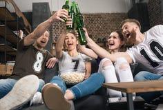 Amis faisant tinter des bouteilles à bière Image libre de droits