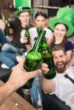Amis faisant tinter des bouteilles à bière Photos libres de droits
