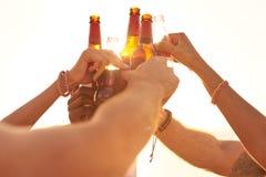 Amis faisant tinter des bouteilles à bière au soleil Images stock