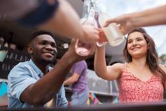 Amis faisant tinter des bouteilles avec des boissons au camion de nourriture Photographie stock libre de droits