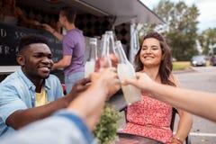 Amis faisant tinter des bouteilles avec des boissons au camion de nourriture Image libre de droits