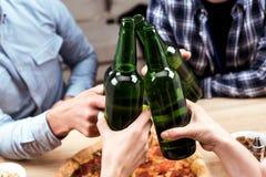 Amis faisant tinter des bouteilles de bière Photos stock