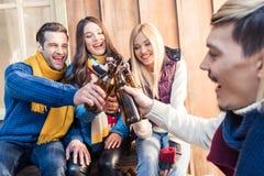 Amis faisant tinter des bouteilles de bière au barbecue Photographie stock libre de droits