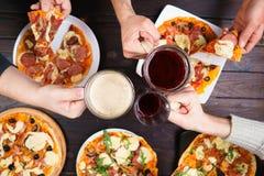 Amis faisant tinter des tasses avec de la bière et mangeant de la pizza Vue supérieure sur le mA Image stock