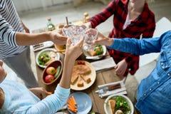 Amis faisant tinter des verres au dîner Images libres de droits