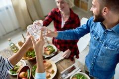 Amis faisant tinter des verres au dîner de thanksgiving Image stock