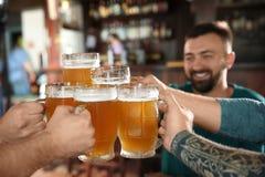 Amis faisant tinter des verres avec de la bière Photo stock