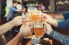 Amis faisant tinter des verres avec de la bière Photos libres de droits
