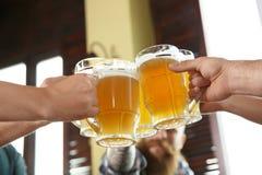 Amis faisant tinter des verres avec de la bière Photographie stock