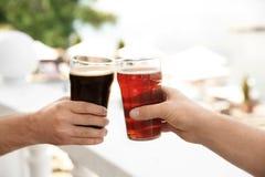 Amis faisant tinter des verres avec de la bière savoureuse Image libre de droits