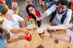 Amis faisant tinter des verres avec des boissons au restaurant Photo stock