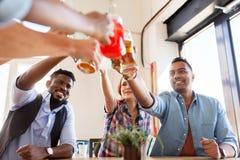 Amis faisant tinter des verres avec des boissons au restaurant Image libre de droits