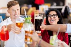 Amis faisant tinter des verres avec des boissons au restaurant Photos stock