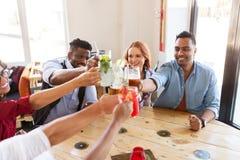 Amis faisant tinter des verres avec des boissons au restaurant Images stock