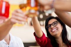 Amis faisant tinter des verres avec des boissons au restaurant Image stock
